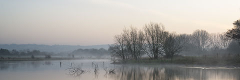 Panorama landscape of lake in mist with sun glow at sunrise Royalty Free Stock Photos