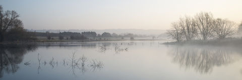 Panorama landscape of lake in mist with sun glow at sunrise Royalty Free Stock Photo