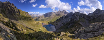 Panorama landscape with a lake in the mountains, huge rocks and. Panorama landscape with clear lake in the mountains, huge rocks and Alpika and reflection of Stock Image