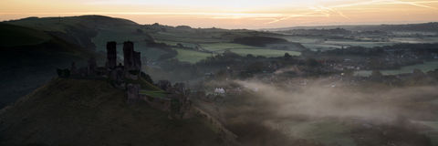 Panorama landscape of medieval castle in misty sunrise morning. Panorama landscape of medieval castle in misty vibrant sunrise morning royalty free stock image