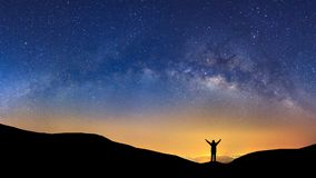 Panorama landscape with milky way, Night sky with stars and silhouette of a standing sporty man with raised up arms on high mount stock photos