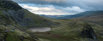 Panorama landscape mountain range at sunset with lake and walker Royalty Free Stock Images