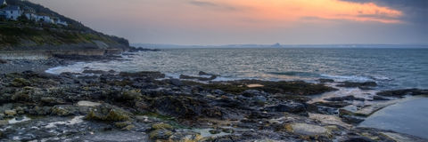 Panorama landscape of rocky coastline at sunrise Stock Photos