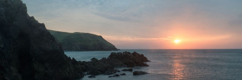 Panorama landscape vibrant sunset over rocky coastline Royalty Free Stock Photography