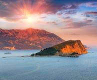 Panorama- landskap av kusten Budva riviera: Sveti Nikola ö och berg på solnedgången Arkivbilder