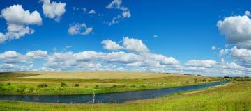 Panorama- landskap för solig sommar med floden, guld- fält, gröna kullar och härliga moln i blå himmel arkivbilder