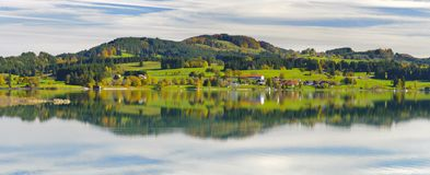 Panorama- landskap i regionen Allgaeu med att avspegla för fjällängbergskedja som är symmetriskt i sjön royaltyfri bild