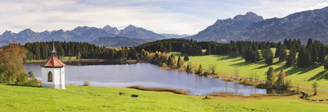 Panorama- landskap i regionen Allgaeu med det lilla kapellet på sjö- och fjällängberg arkivfoton