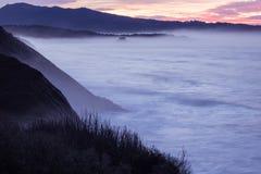 Panorama- landskapsikt efter solnedgång på den atlantiska kustlinjen i rosa himmel med enorma vågor, basque land, Frankrike royaltyfri fotografi