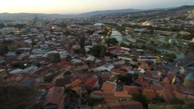 Panorama of large city in dusk light, mountains on horizon, beautiful cityscape. Stock footage stock video footage