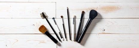 Panorama largo para la exhibición de los cepillos profesionales del maquillaje sobre la madera Imagen de archivo