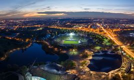 Panorama of the lit Olympiapark from above with light trails fro. M traffic during sunset royalty free stock photo