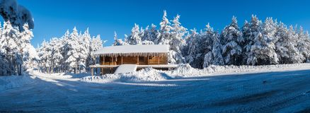 Panorama with a log cabin covered in a snowy forest Stock Image