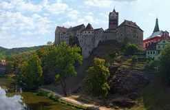Panorama of Loket Castle at the top of the rocky hill with Ohre River and colorful medieval buildings by summer sunny day. Bohemia, Sokolov, Karlovarsky Region royalty free stock photography