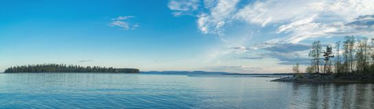 Panorama of low tide in the Kandalaksha Bay. Coastal wooded islands and calm sea in the Kandalaksha Bay royalty free stock images