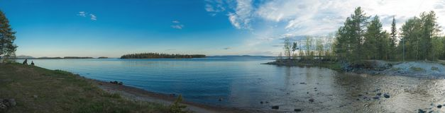 Panorama of low tide in the Kandalaksha Bay. Coastal wooded islands and calm sea in the Kandalaksha Bay stock images