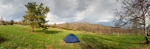 Panorama of the lush green spring meadows, tent and trees Royalty Free Stock Photography