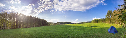 Panorama of the lush green spring meadows, tent and trees Royalty Free Stock Photo