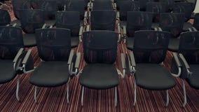 Panorama móvel de cadeiras do convidado na primeira fileira Esperando os espectadores e os ouvintes Salão vazio do congresso com filme