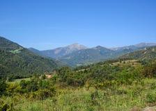 Panorama magnífico con las montañas del macizo de Conigou, la vegetación verde y el cielo azul, los Pirineos del verano de Franci fotos de archivo libres de regalías