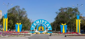 Panorama of the Main Avenue with colorful Emblem and Flag of City Temirtau on the End of the main Promenade. Entrance from royalty free stock photography