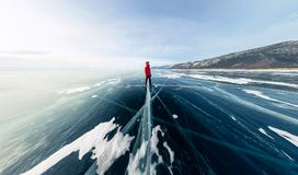 Panorama man stand on cracks on blue ice of Lake Baikal from Olkhon.  royalty free stock photos