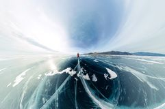 Panorama man stand on cracks on blue ice of Lake Baikal from Olkhon.  royalty free stock photo