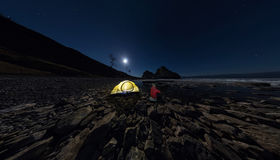 Panorama of  man at  tent on  stone beach on shore of Lake Ba Stock Image