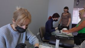 Panorama of manicure retraining courses. Manicure teacher observes the work of his students stock video