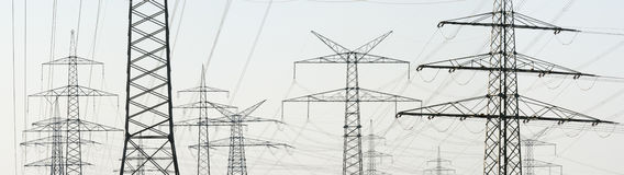 Panorama of many electric pylons for energy supply. Panorama view to many electric poles of power station Royalty Free Stock Image