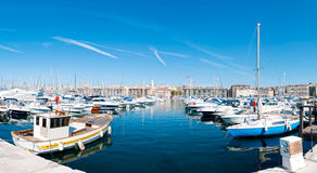 Panorama of the Marseille port. Panorama of the port of Marseille (Marseilles). Small private boats in foreground with deep blue water of the harbor, blue sky Royalty Free Stock Photos