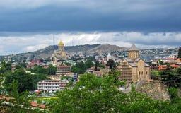 Panorama med domkyrkan för helig Treenighet av Tbilisi och kyrkan för Metekhi St-oskuld från Narikala den forntida fästningen, Tb arkivfoton