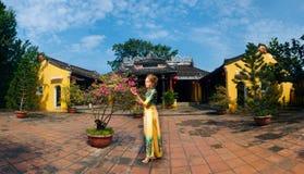 Panorama med flickan i traditionell vietnamesisk klänning i Hoi An Arkivfoto
