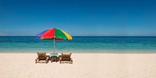 Panorama med ljusa paraply- och strandstolar med copyspace Royaltyfria Bilder
