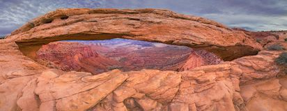 Panorama of Mesa Arch on a cloudy day, Canyon Lands National Park, USA. Panorama of Mesa Arch on a cloudy day with canyons in background, Canyon Lands National Stock Photo