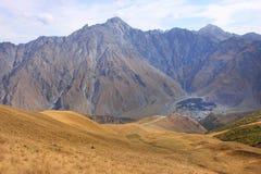 Panorama met de Drievuldigheidskerk van Stephantsminda en Gergeti-(Georgië) Stock Foto's