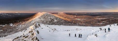 Panorama mit Gruppe Touristen, die in den Winterbergen wandern Lizenzfreie Stockfotografie