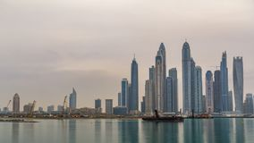 Panorama of modern skyscrapers in Dubai city at sunrise timelapse from the Palm Jumeirah Island. Dubai, United Arab Emirates. Dubai marina in clouds at early stock footage
