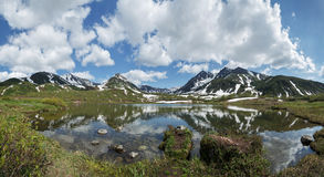 Panorama: montanhas, lago da montanha e nuvens no céu azul no dia ensolarado Imagem de Stock