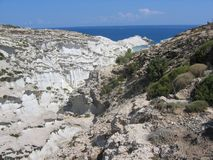 Panorama of moon white rocks coast with mediteranea forest and in distance a blue sea of Milos island in Greece Stock Photo