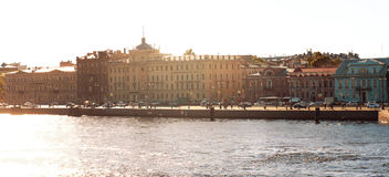 Panorama of the morning sun illuminates the city street and houses standing on the embankment of the river, passers-by go to work Royalty Free Stock Images