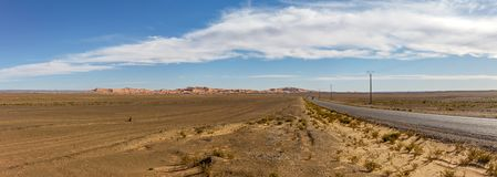 Panorama of Moroccan desert with Erg Chebbi. Moroccan desert road leading to Merzouga and the sand dunes of Erg Chebbi stock photography