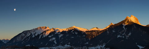Panorama of mountain chain with lighted summits. In winter Stock Photography