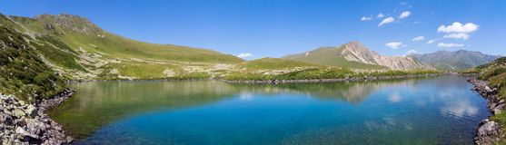 Panorama mountain lake in Alps. Mountain lake in the Caucasian Alps in late summer Royalty Free Stock Images