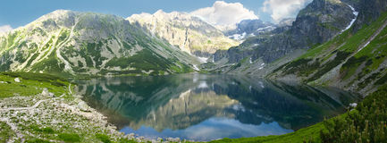 Panorama of mountain lake. Panorama of a mountain lake on the background of the craggy mountain slopes royalty free stock photos