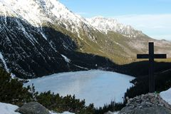 Panorama of a mountain lake with a cross in the foreground.  Stock Images