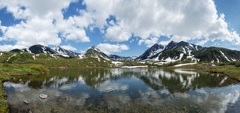 Panorama: mountain lake, mountains and clouds in blue sky on sunny day Royalty Free Stock Photography