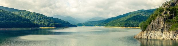 Summer scenery. of Vidraru Lake and Dam glowing in sunlight. loc. Panorama of mountain lake with overcast sky. hills glowing in sunlight. creative image. retro royalty free stock photography