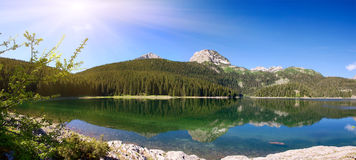 Panorama of mountain lake with reflections Stock Photos