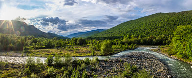 Panorama of mountain landscape of Abkhazia river at sunset. Wide panorama of mountain landscape of Abkhazia river at sunset with beautiful clouds, haze, a sun is stock image
